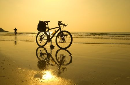 The black bicycle of a traveling cyclist resting a the beach
