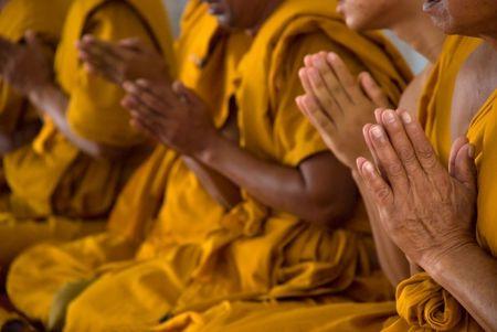 The hands of praying Thai Buddhist monks.