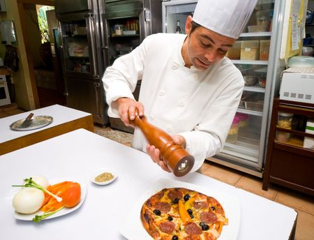 An Italian pastry chef preparing a cheese, olive and pepperoni pizza in a restaurant kitchen