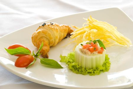 A tuna and cucumber appetizer served with a croissant fries on a triangular white porcelain plate