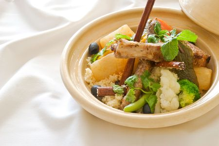tradition: Close-up image of a Couscous in a beige tajine pot served with mint, cinnamon and parsley