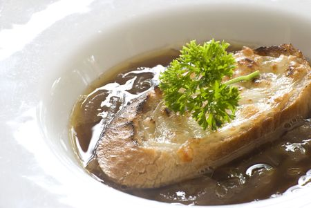 A serving of hot French onion soup topped with a slice of toasted French bread and a branch of parsley, served in a white ceramic bowl.  Фото со стока