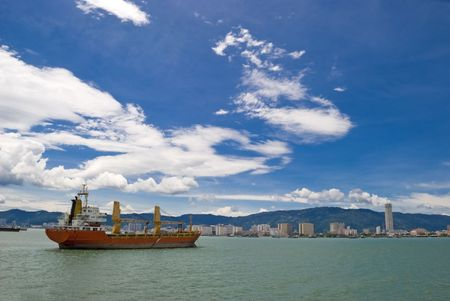 A large red cargo shipping vessel going through a strait and into the port of Penang in Malaysia.  Фото со стока