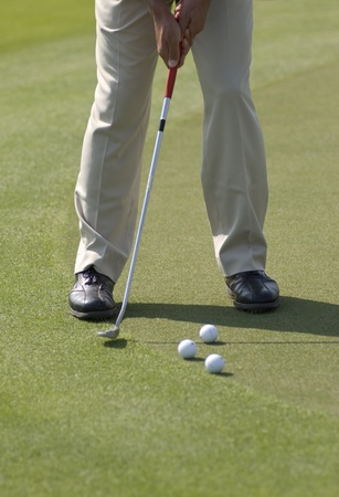 A golfer wearing beige pants and black leather shoes practicing his putt with several balls on a sunny day photo