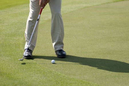 A golfer wearing beige pants and black leather shoes practicing his putt on a sunny day photo