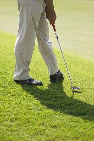 A golfer wearing beige pants and black leather shoes practicing his putt without a ball on a sunny day photo