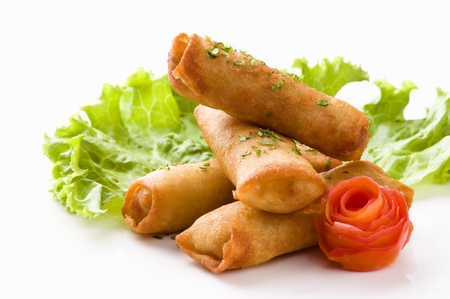A horizontal image of four egg rolls sprinkled with parsley served on a white ceramic plate with a leaf of lettuce and a flower shaped tomato Banco de Imagens
