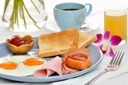 Eggs, bacon and sausages served with toast with strawberry jam served on a blue ceramic plate accompanied by coffee, pineapple juice and an orchid