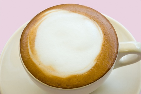 Cappuccino coffee served in a white ceramic cup against a pink background