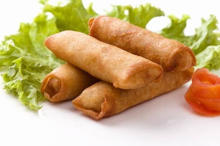 A horizontal image of four egg rolls served on a white ceramic plate with a leaf of lettuce and a flower shaped tomato  Stock Photo