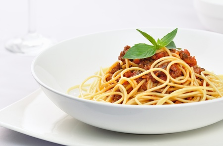 Spaghetti covered with bolognese sauce, topped with basil and served on a white ceramic bowl Imagens