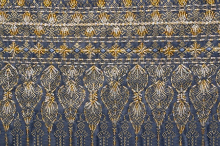 thailand silk: A detail image of blue and yellow floral patterns in Thai silk fabric made with thread and beads