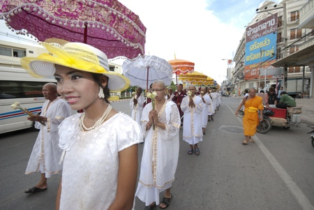 ordain: HUA HIN, Thailand - OCTOBER 25, 2011. A young woman leads a procession of newly ordained Buddhist monks on October 25, 2011 in Hua Hin, Thailand. Monk ordinations in Thailand are very important social events. Editorial