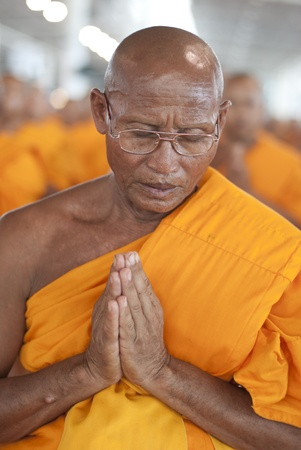 introspection: BANGKOK, SEPTEMBER 22. A Thai Buddhist monk meditates during a mass spiritual event at the Dhammakaya temple north of Bangkok in Thailand on September 22, 2011. The Dhammakaya temple is the largest religious physical structure in the world although it is