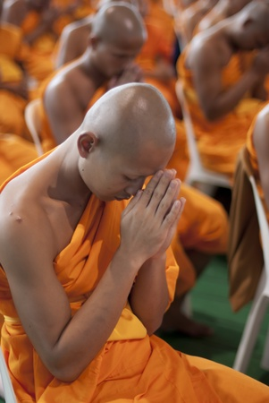 BANGKOK, SEPTEMBER 22. A young Thai Buddhist monk prays during a mass spiritual event at the Dhammakaya temple north of Bangkok in Thailand on September 22, 2011. The Dhammakaya temple is the largest religious physical structure in the world although it i Stock Photo - 11249435