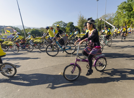 hundreds and thousands: Chiang Mai, Thailand - December 11, 2015: A woman from a Hmong Hilltribe rides among other cyclists at the Bike For Dad event on December 11, 2015 in Chiang Mai, Thailand. The Bike For Dad cycling event attracts hundreds of thousands of cyclists and is he