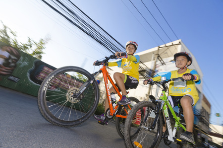 motherly: Chiang Mai, Thailand - December 11, 2015: A young boy rides with his mother among other cyclists at the Bike For Dad event on December 11, 2015 in Chiang Mai, Thailand. The Bike For Dad cycling event attracts hundreds of thousands of cyclists and is held  Editorial