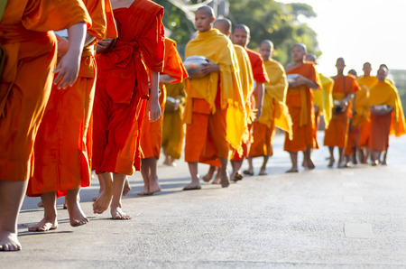 attend: Chiang Mai, Thailand - December 26, 2015: Young Buddhist monks attend a special alms offering ceremony organized for 10,000 monks by Wat Phra Dhammakaya on December 26, 2015 in Chiang Mai, Thailand. Editorial