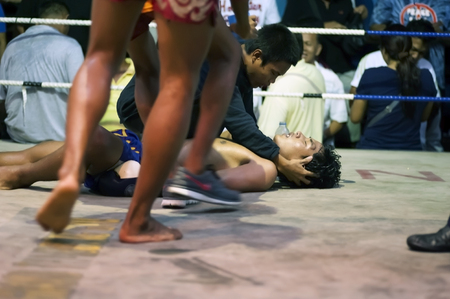 opponent: Hua Hin, Thailand - January 8, 2016: A Muay Thai boxer lies unconscious after receiving a knock out punch from his opponent during a fight at the boxing stadium in Hua Hin, Thailand on January 8, 2016. Muay Thai boxing is considered by many as the nationa Editorial