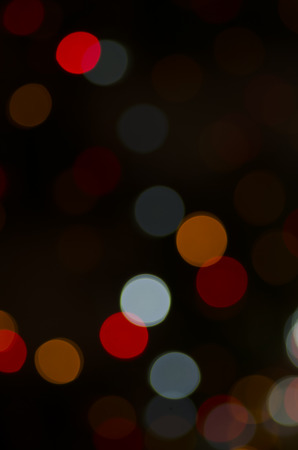 A photographic image of out of focus red, orange and white lights.