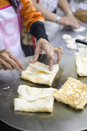 Women making roti pastries at a street food stand in Chiang Mai, Thailand. Фото со стока