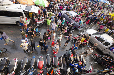 Chiang Mai, Thailand - April 14, 2014: Several people walk on the street as they take part in the Songkran festival in Chiang Mai, Thailand on April 14, 2014. Редакционное