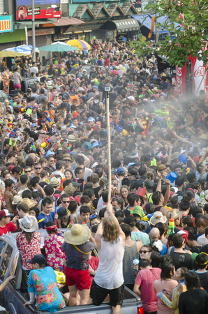 Chiang Mai, Thailand - April 14, 2014: A young man films a large group of people with a GoPro camera during the Songkran festival in Chiang Mai, Thailand on April 14, 2014.