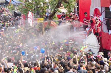 Chiang Mai, Thailand - April 14, 2014: A group of people is sprayed with water by staff at the Air Asia stage at the Songkran festival in Chiang Mai, Thailand on April 14, 2014. Редакционное