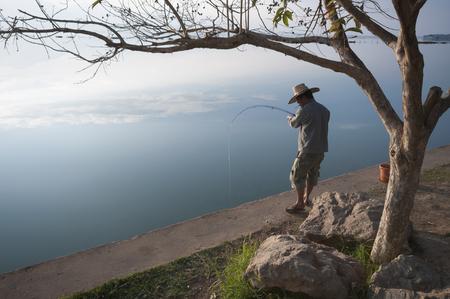 Phayo, Thailand - December 29, 2011: A man fishes at a lake in Phayo, Thailand on December 29, 2011. Редакционное