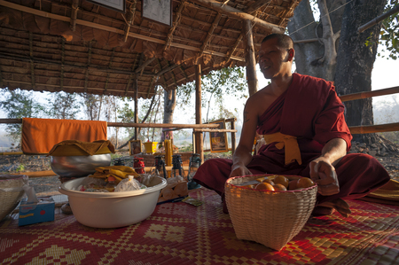 Pai, Thailand - February 17, 2016: A Theravada Buddhist monk sits in his forest bamboo hut in the woods near the village of Pai, Thailand on February 17, 2016.