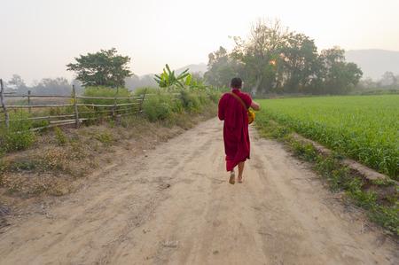 Pai, Thailand - February 21, 2016: A Theravada Buddhist walks on a rural path through a field near Pai, Thailand on February 21, 2016. Редакционное