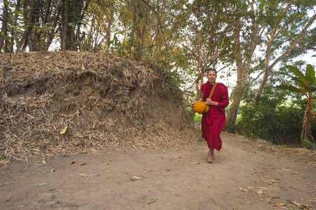 Pai, Thailand - February 21, 2016: A Theravada Buddhist walks on a forest path in the woods near Pai, Thailand on February 21, 2016.