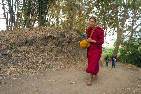Pai, Thailand - February 21, 2016: A Theravada Buddhist walks on a forest path with followers in the woods after receiving morning alms near Pai, Thailand on February 21, 2016. Редакционное