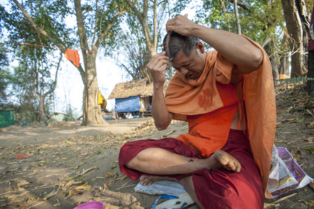 Pai, Thailand - February 21, 2016: A Theravada Buddhist shaves his head in a forest near Pai, Thailand on February 21, 2016.