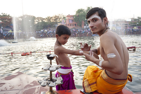 madhya: Ujjain, Madhya Pradesh, India - May 18, 2016: A young priest paints the arm of a boy-apprentice before a fire ceremony called �aarti� at the Kshipra River during the Kumbh Mela religious festival in Ujjain, India on May 18, 2016. The Kumbh M