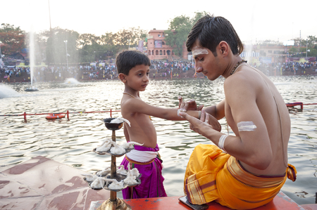 madhya pradesh: Ujjain, Madhya Pradesh, India - May 18, 2016: A young priest paints the arm of a boy-apprentice before a fire ceremony called �aarti� at the Kshipra River during the Kumbh Mela religious festival in Ujjain, India on May 18, 2016. The Kumbh M