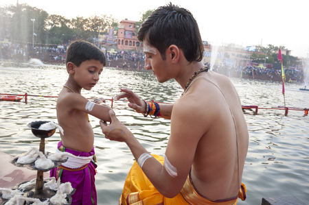 madhya: Ujjain, Madhya Pradesh, India - May 18, 2016: A young priest paints the arm of a boy-apprentice before a fire ceremony called �aarti� at the Kshipra River during the Kumbh Mela religious festival in Ujjain, India on May 18, 2016. Kumbh Mela