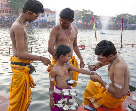 Ujjain, Madhya Pradesh, India - May 18, 2016: A young priest paints the arm of a boy-apprentice before a fire ceremony called �aarti� at the Kshipra River during the Kumbh Mela religious festival in Ujjain, India on May 18, 2016. The Kumbh M