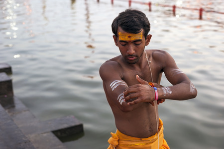 Ujjain, Madhya Pradesh, India - May 18, 2016: A young priest paints his arm before a fire ceremony called �aarti� at the Kshipra River during the Kumbh Mela religious festival in Ujjain, India on May 18, 2016. Kumbh Mela is the largest gathe