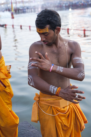 madhya pradesh: Ujjain, Madhya Pradesh, India - May 18, 2016: A young priest paints his arm before a fire ceremony called �aarti� at the Kshipra River during the Kumbh Mela religious festival in Ujjain, India on May 18, 2016. Kumbh Mela is the largest gathe Editorial