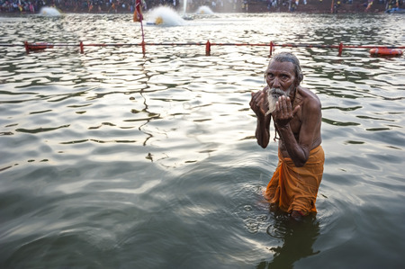 Ujjain, Madhya Pradesh, India - May 18, 2016: An old man bathes in the Kshipra River during the Kumbh Mela religious festival in Ujjain, India on May 18, 2016. The Kumbh Mela is the largest event on Earth, which attracts millions of Hindu worshippers over