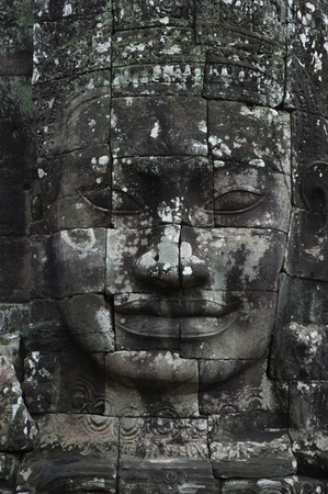 A vertical photographic image of a large sculpted stone face of the Buddha at Bayon Temple in Angkor Thom, which is close to Angkor Wat near Siem Reap in Cambodia. Фото со стока