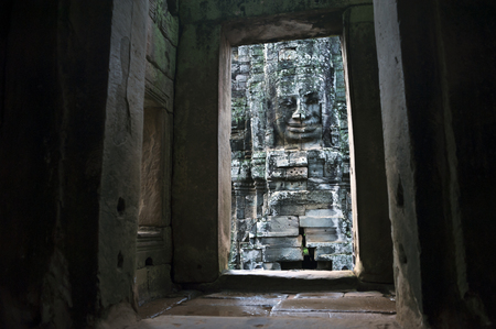 An horizontal photographic image of a large sculpted stone face of the Buddha at Bayon Temple in Angkor Thom, which is close to Angkor Wat near Siem Reap in Cambodia.