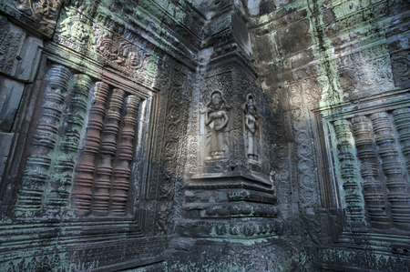 cambodia sculpture: An horizontal photographic image of a 2 female deities at Ta Prohm, which is part of the larger Angkor Wat temple complex near Siem Reap in Cambodia. Stock Photo