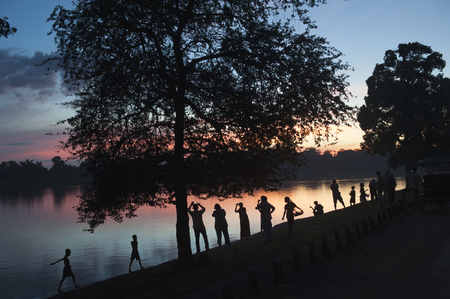 An horizontal image of people photographing a sunset over a lake with their mobile phones.