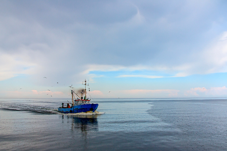 The fishing vessel seagulls escorted back to shore Stock Photo