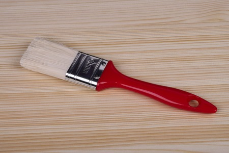 tassel witassel with red handle lies on a wooden boardth red handle lies on a wooden board