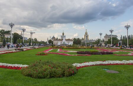 Moscow, VDNKh September 02, 2019 view of a beautiful working fountain and many roses near it in VDNH park on a cloudy fall day