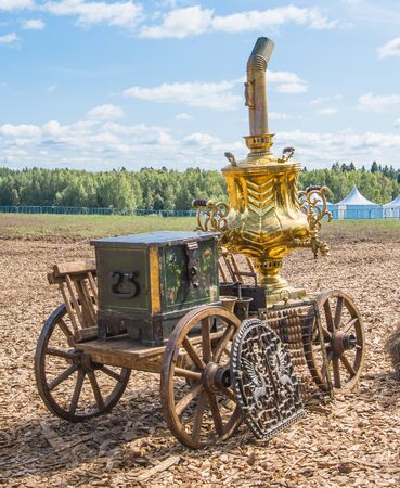 a huge golden samovar stands on a cart, next to it is a large wooden chest photo made in a field in nature on a sunny summer day