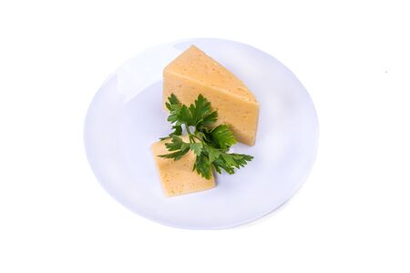 piece of cheese on a white plate with a sprig of parsley, top view on a white isolated background Фото со стока - 131800974